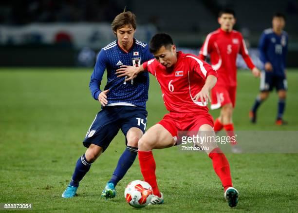Ito Junya of Japan and Kang Kuk Chol of North Korea in action during the EAFF E1 Men's Football Championship between Japan and North Korea at...
