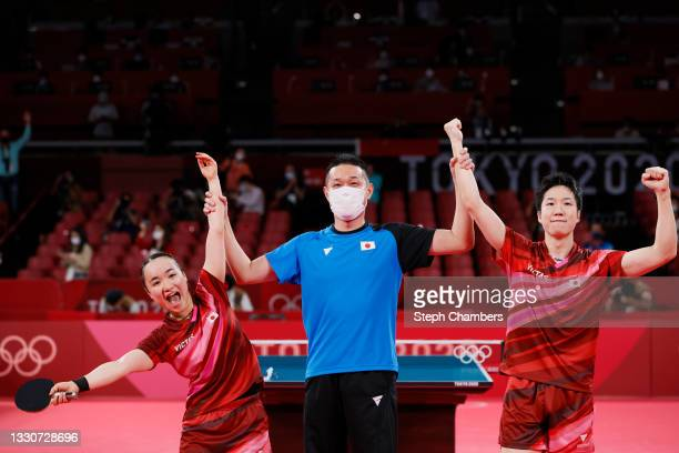 Ito Mima and Jun Mizutani of Team Japan celebrate with their coach after winning their Mixed Doubles Gold Medal match on day three of the Tokyo 2020...