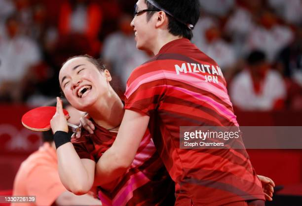 Ito Mima and Jun Mizutani of Team Japan embrace after winning their Mixed Doubles Gold Medal match on day three of the Tokyo 2020 Olympic Games at...