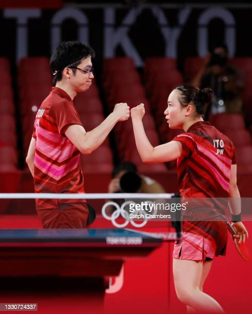 Ito Mima and Jun Mizutani of Team Japan fist bump during their Mixed Doubles Gold Medal match on day three of the Tokyo 2020 Olympic Games at Tokyo...