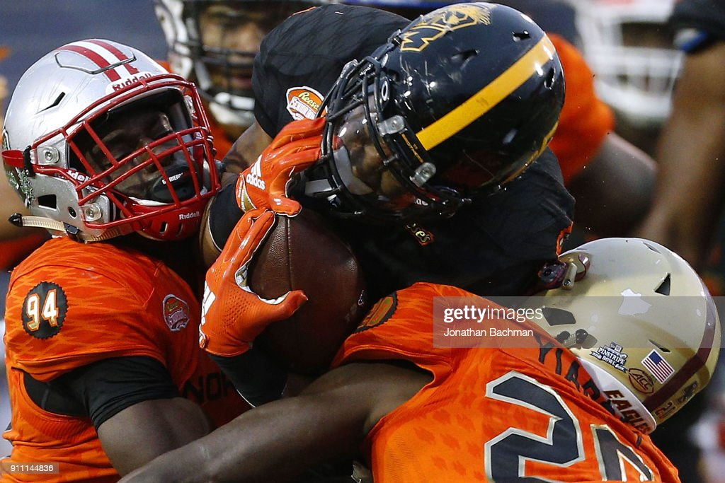 Ito Smith #25 of the South team is tackled by Greg Gilmore #94 of the South team and Isaac Yiadom #20 during the second half of the Reese's Senior Bowl at Ladd-Peebles Stadium on January 27, 2018 in Mobile, Alabama.