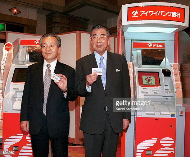 ItoYokado Co's president Toshifumi Suzuki right and IYBank's Takashi Anzai hold up bank cards in front of automated teller machines May 1 2001 at a...