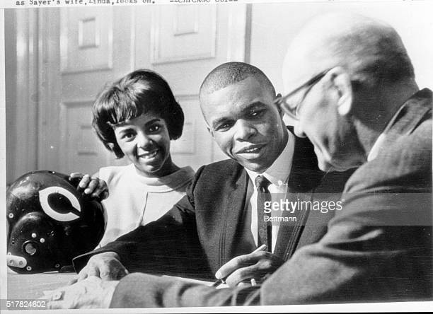 It's a threeway smile as Gale Sayers agrees to become a member of the Chicago Bears Sayers Bears' second draft choice a star at the Kansas University...