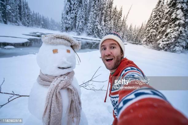 it's christmas time - man taking selfie with snowman on winter vacations - só um homem imagens e fotografias de stock