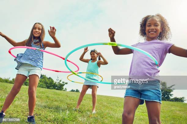 it's hard not to be happy when you're hula hooping - kids playground stock photos and pictures
