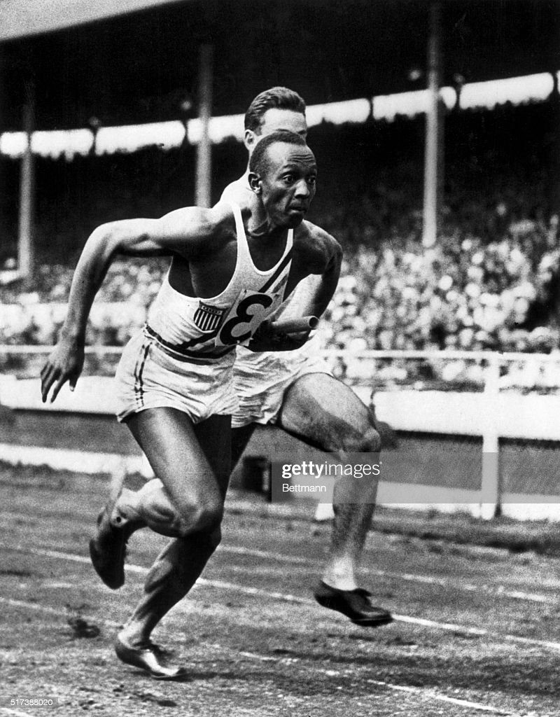 It's Owens again. London, England: Jesse Owens, fresh from his triumphs in the Olympics, is shown taking over the baton from M.I. Glickman, in the 400 yard relay, won by the United States in the track meet against a British team at the White City Stadium in London, recently. The United States won the meet by 11 events to 3.
