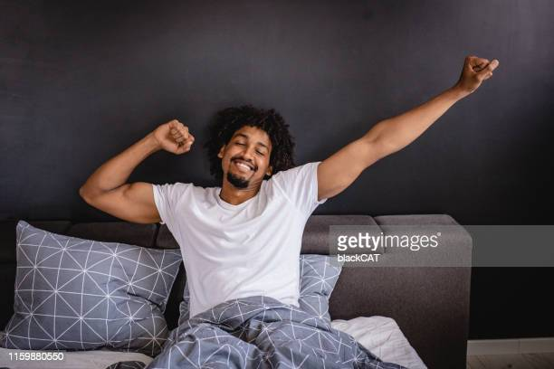 it's time to wake up - black man sleeping in bed stock pictures, royalty-free photos & images