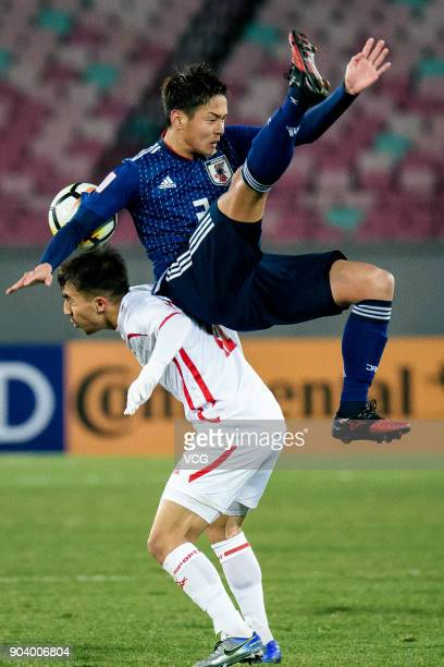 Itsuki Urata of Japan and Mohammad ElKayed of Palestine compete for the ball during the AFC U23 Championship Group B match between Japan and...