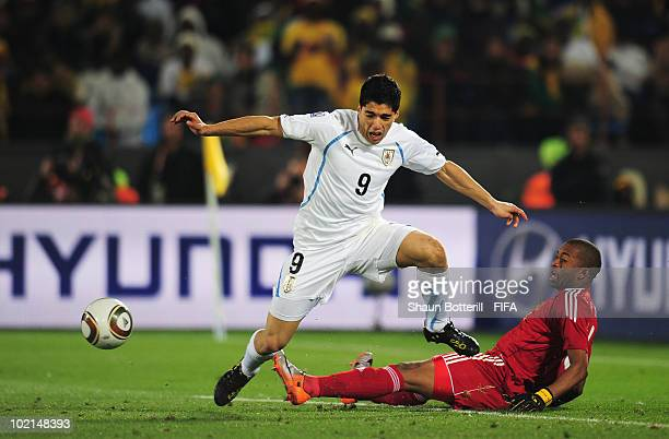 Itumeleng Khune of South Africa tackles Luis Suarez of Uruguay and is sent off straight away during the 2010 FIFA World Cup South Africa Group A...