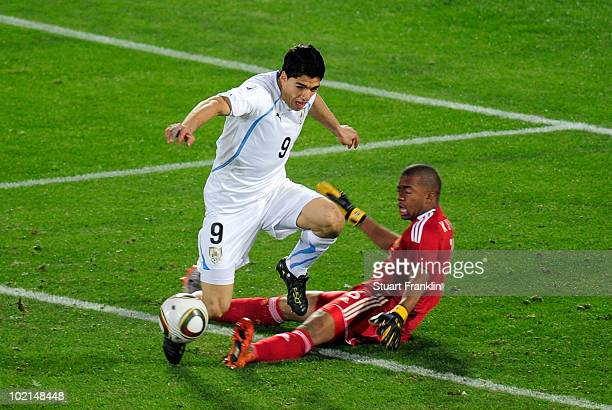 Itumeleng Khune of South Africa tackles Luis Suarez of Uruguay, for which he receives a red card, during the 2010 FIFA World Cup South Africa Group A...
