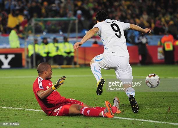 Itumeleng Khune of South Africa tackles Luis Suarez of Uruguay for which he receives a red card during the 2010 FIFA World Cup South Africa Group A...