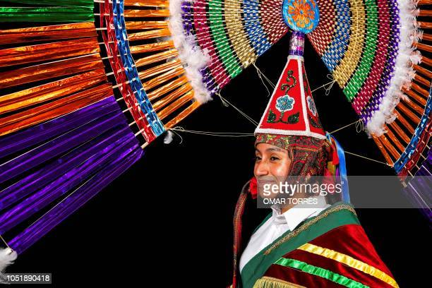Itzel Valiente Cruz poses for a photograph with her 'Penacho' traditional costume during the presentation of the Huey Atlixcayotl Festival on...