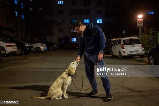 Iulian Barbulescu 34 years old poses for a portrait during one of the daily walks outside with his 5monthold dog Jesse on March 28 2020 in Bucharest...
