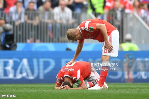 Iury Gazinsky of Russia checks on teammate Alan Dzagoev of Russia as he goes down injured during the 2018 FIFA World Cup Russia Group A match between...