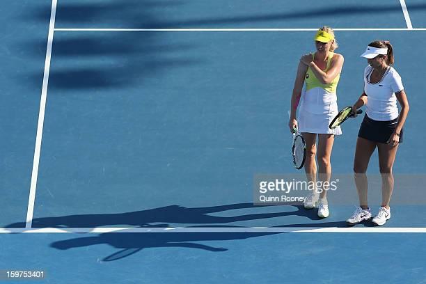 Iva Majoli of Croatia and Barbara Schett Austria talk tactics in their legends doubles match against Martina Navratilova of the United States of...