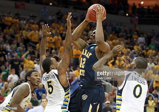 Ivan Aska of the Murray State Racers shoots the ball between Jae Crowder Junior Cadougan and Jamil Wilson of the Marquette Golden Eagles in the...