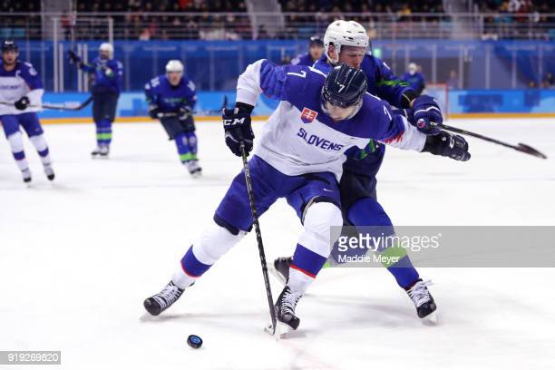 Ivan Baranka of Slovakia shields the puck from Jan Urbas of Slovenia during the Men's Ice Hockey Preliminary Round on Day 8 of on day eight of the...