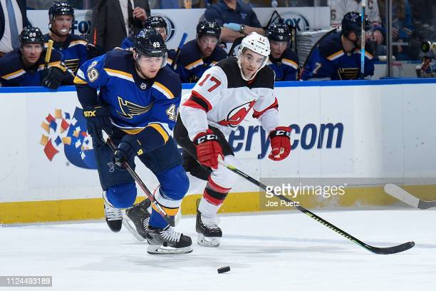 Ivan Barbashev of the St Louis Blues and Kenny Agostino of the New Jersey Devils battle for the puck at Enterprise Center on February 12 2019 in St...