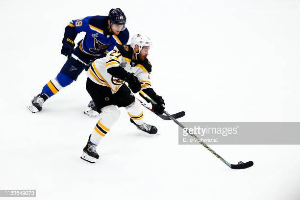 Ivan Barbashev of the St Louis Blues pursues John Moore of the Boston Bruins in Game Four of the 2019 NHL Stanley Cup Final at Enterprise Center on...