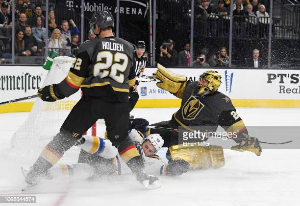 Ivan Barbashev of the St Louis Blues slides past MarcAndre Fleury and Nick Holden of the Vegas Golden Knights after taking a shot on goal in the...