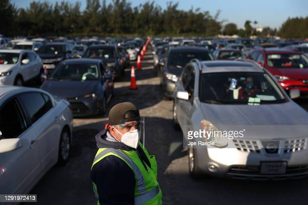 Ivan Cantero, who works for the City of Hialeah, directs traffic as the city distributes 5,000 grocery gift cards worth $250 each to people in need...