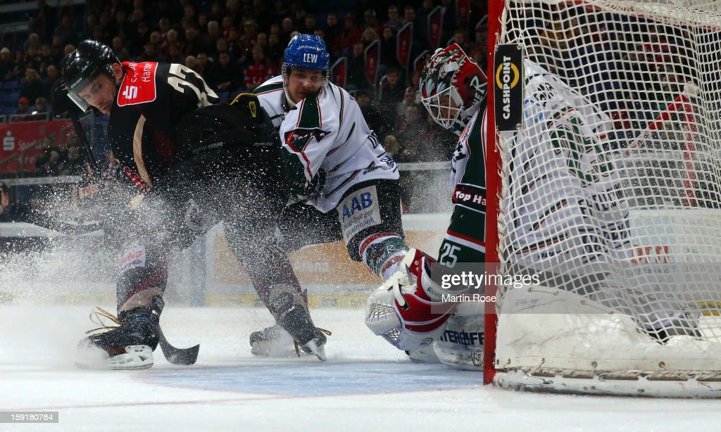Ivan Ciernik (L) of Hannover and Sergio Somma (C) of Augsburg battle for the puck in front of the net during the DEL match between Hannover Scorpions and Augsburger Panther at TUI Arena at TUI Arena on January 9, 2013 in Hanover, Germany.
