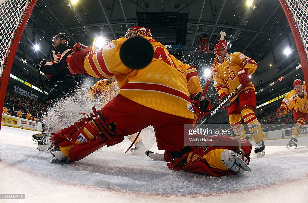 Ivan Ciernik (L) of Hannover scores his team's opening goal over Robert Goepfert (C), goaltender of Duesseldorf during the DEL match between Hannover Scorpions and Duesseldorfer EG at TUI Arena on November 23, 2012 in Hanover, Germany.