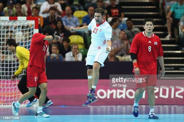 Ivan Cupic of Croatia celebrates a point while DukJun Lim and Junggeu Park of Korea look dejected during the Men's Handball preliminaries group B...