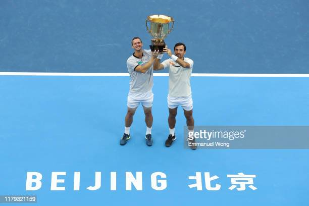 Ivan Dodig of Croatia and Filip Polasek of Slovakia pose with the trophy during the medal ceremony after their Men's doubles final match against...