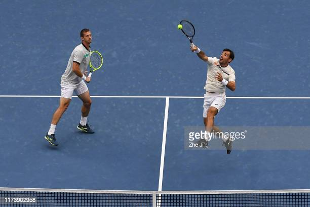 Ivan Dodig of Croatia and Filip Polasek of Slovakia return a shot during their Men's doubles final match of 2019 China Open against Lukasz Kubot of...