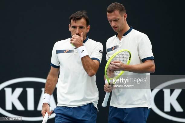 Ivan Dodig of Croatia and Filip Polasek of Slovakia talk tactics during their Men's Doubles first round match against Blake Ellis and Alexei Popyrin...