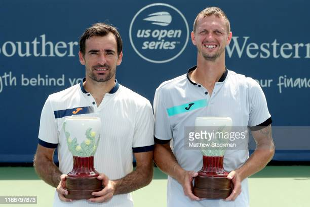 Ivan Dodig of Croatia and Ivan Polasek of Slovakia pose for photographers after winning the men's doubles final during the Western & Southern Open at...