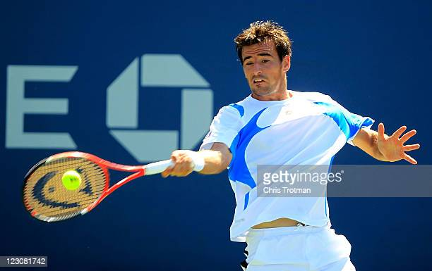 Ivan Dodig of Croatia returns a shot against Nikolay Davydenko of Russia during Day Two of the 2011 US Open at the USTA Billie Jean King National...