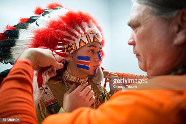 Ivan Dozier Sr right puts a headdress on student Omar Cruz as he prepares to portray Chief Illiniwek during halftime at a University of Illinois...