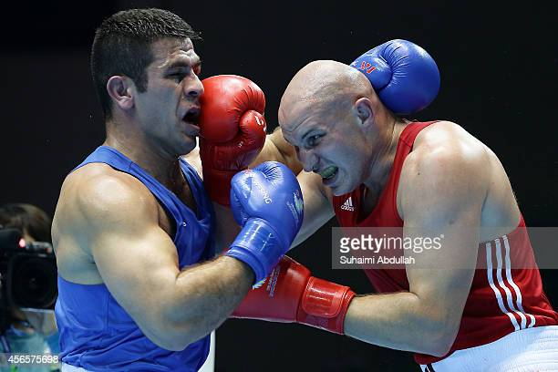 Ivan Dychko of Kazakhstan fights Jasem Delavari of Iran during the Men's Super Heavyweight Final on day fourteen of the 2014 Asian Games match at...