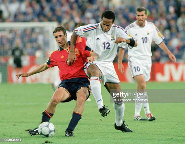 Ivan Helguera of Spain is challenged by Thierry Henry of France during a UEFA Euro 2000 Quarter Final match at the Jan Breydel Stadium on June 25,...