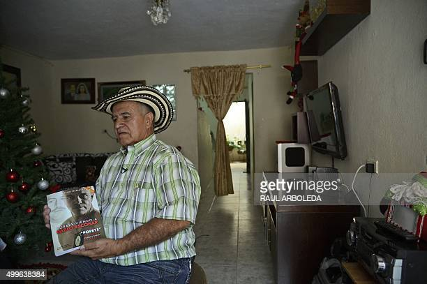 Ivan Hernandez , a resident of the Pablo Escobar neighborhood shows a book written by Pablo Escobar's hitmen chief A.K.A, Popeye, at his home in the...