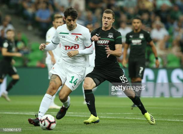 Ivan Ignatyev of FC Krasnodar vies for the ball with Vedran Corluka of FC Lokomotiv Moscow during the Russian Premier League match between FC...