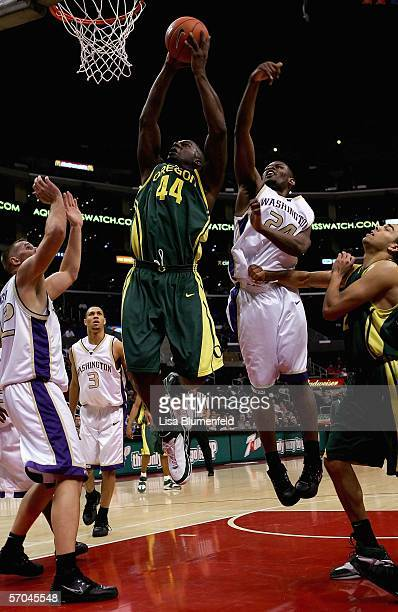 Ivan Johnson of the Oregon Ducks goes to the basket past Mike Jensen and Jamaal Williams of the Washington Huskies in the second half of their...