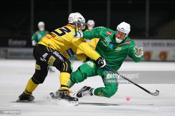 Ivan Lebedev of Hammarby Bandy is tackled by Robin Redin of Broberg/Soderhamn Bandy during the Elitserien bandy match between Hammarby Bandy and...