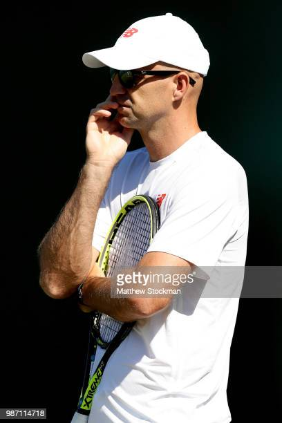 Ivan Ljubicic watches Roger Federer of Switzerland practice on court during training for the Wimbledon Lawn Tennis Championships at the All England...