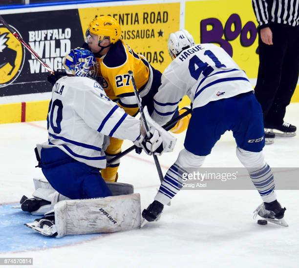 Ivan Lodnia of the Erie Otters runs into Emanuel Vella and Nicolas Hague of the Mississauga Steelheads during game action on November 15 2017 at...