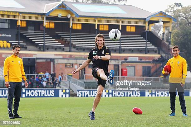 Ivan Maric of the Tigers kicks a soccer ball between Hernanes and Paulo Dybala of Juventus during a Richmond Tigers AFL and Juventus FC media...