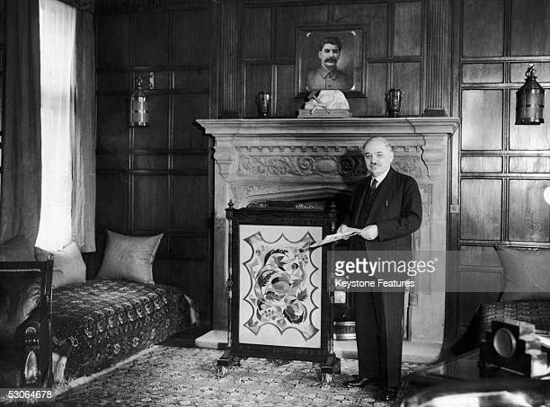 Ivan Mikhailovich Maisky the Soviet Ambassador to Britain standing by the fireplace of his study at the Russian Embassy in London 1941 Above the...