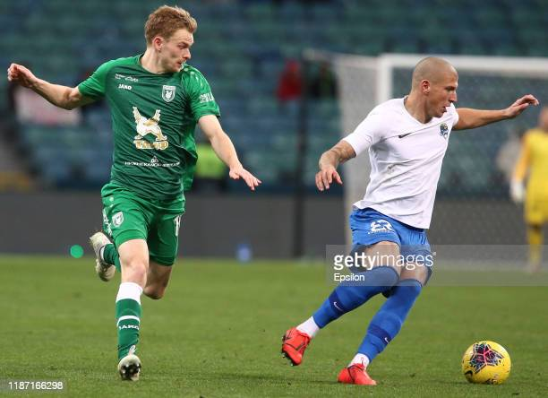 Ivan Miladinovic of PFC Sochi vies for the ball with Pavel Mogilevets of FC Rubin Kazan during the Russian Premier League match between PFC Sochi v...