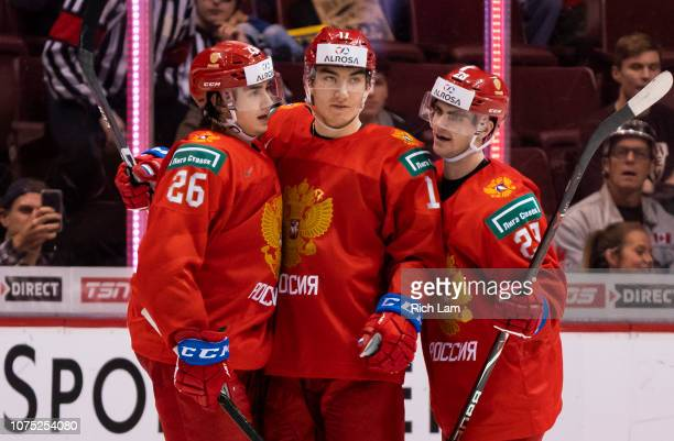Ivan Morozov of Russia celebrates with teammates Alexander Romanov and Kirill Slepets after scoring a goal against Denmark in Group A hockey action...