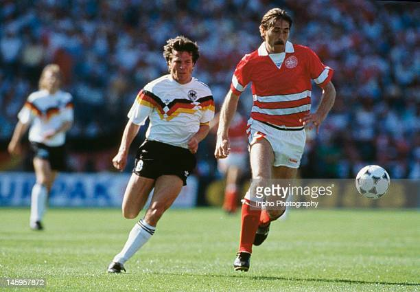 Ivan Nielsen of Denmark reaches the ball ahead of Lothar Matthaus of West Germany during the UEFA European Championships 1988 Group 1 match between...