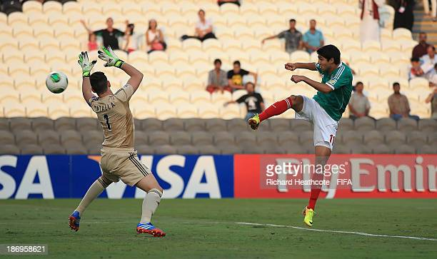 Ivan Ochoa of Mexico shoots past Augusto Batalla of Argentina to score the opening goal during the FIFA U17 World Cup UAE 2013 Semi Final match...