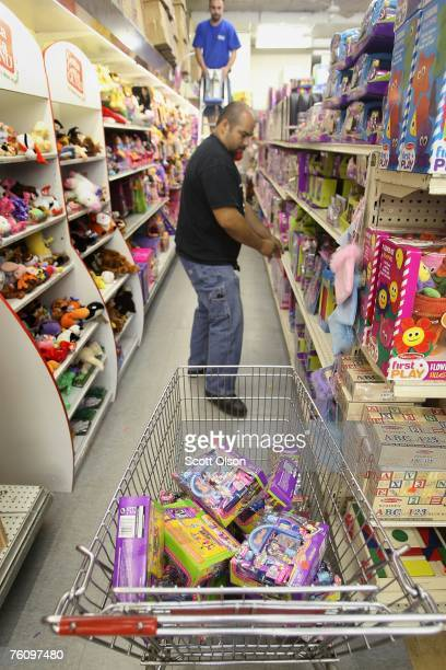 Ivan Ortega fills a shopping cart with recalled toys being pulled from the shelves at the Cut Rate Toys toy store August 14 2007 in Chicago Illinois...