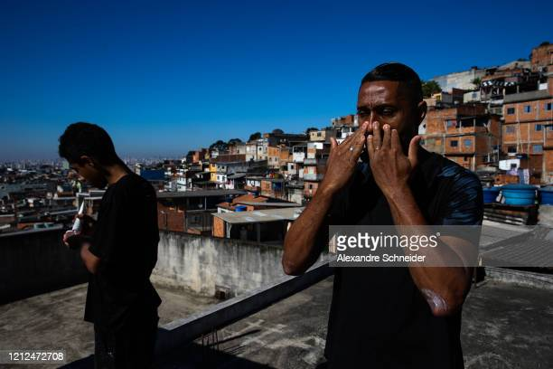 Ivan Pereira do Nascimento 39 years old applies sunscreen before conducting training sessions from the roof of his house to residents of Brasilandia...